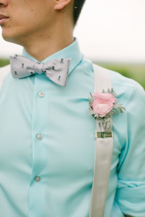 a mint blue shirt, cream suspenders, a printed bow tie
