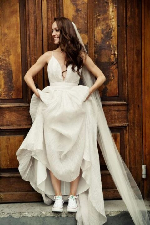 a modern bridal look with a spaghetti strap A-line wedding dress, a long veil and white Converse