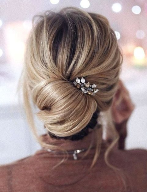 a modern elegant bridesmaid updo with a low chignon, locks down and a rhinestone hairpiece