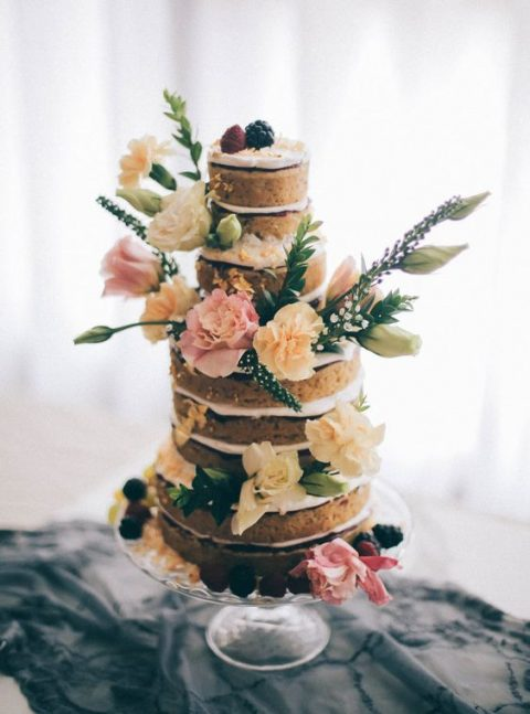 a naked vegan gluten-free wedding cake topped with fresh berries, blooms and some greenery