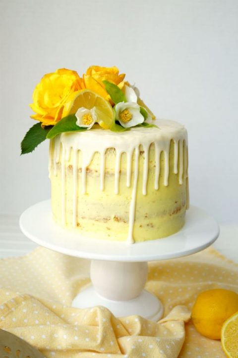 a naked vegan lemon curd layer cake with yellow frosting, dripping and some blooms and citrus on top