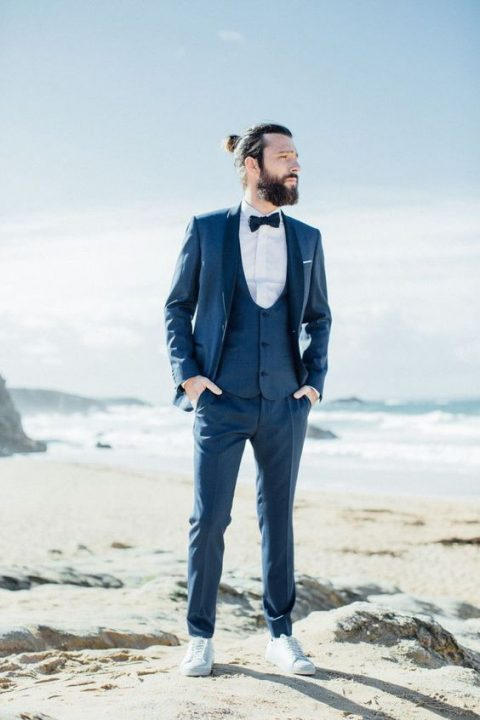 a navy htee-piece suit with a white shirt, a navy bow tie and white sneakers