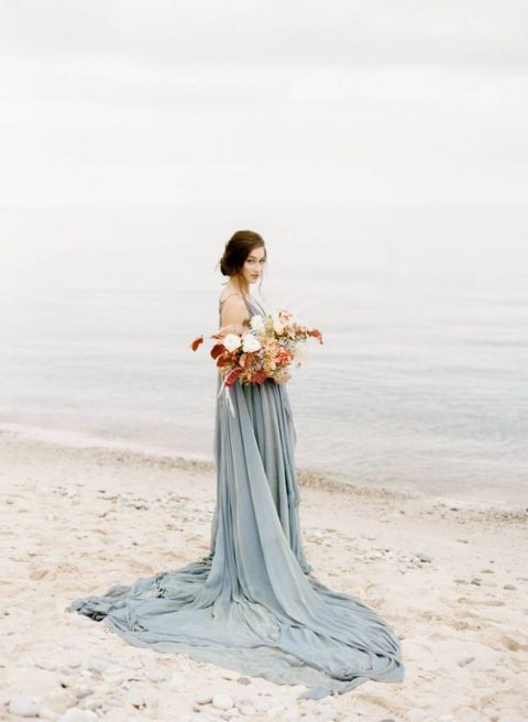 a powder blue strap wedding dress with a deep neckline and a train