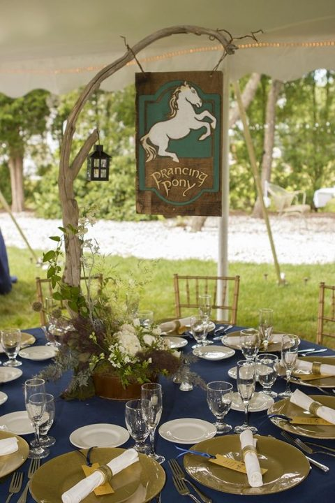 a reception table decorated in navy and green, with a branch centerpiece, a lantern and a sign with the name of the tavern
