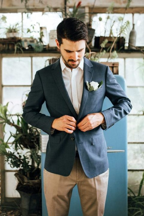 a relaxed look with a white shirt, a navy blazer and tan pants plus a flower in the pocket