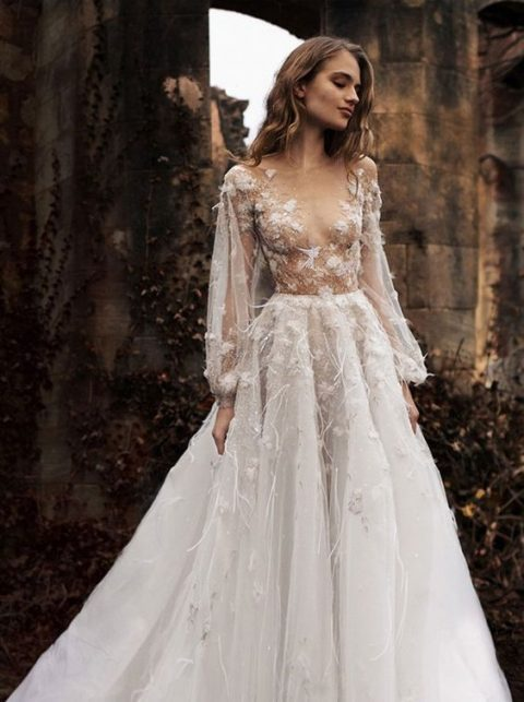 a romantic A-line wedding dress with a sheer bodice, long sleeves and floral appliques