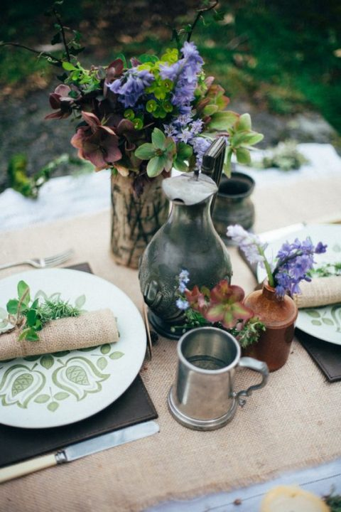 a rustic table inspired by hobbits, with green patterned plates, burlap, leather and simple blooms