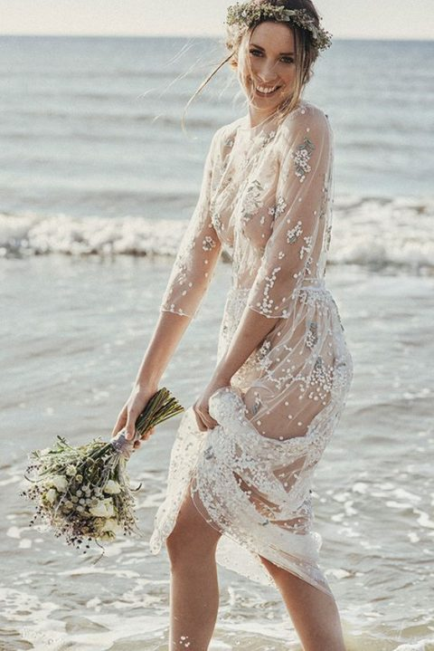 a sheer wedding gown with floral embroidery, a high neckline and long sleeves for beach bride