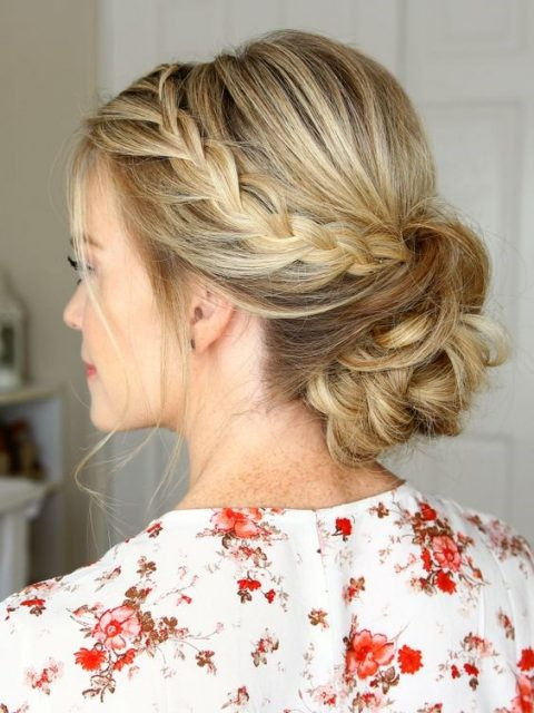 a side braid coming into a low bun and a bump plus some curls down