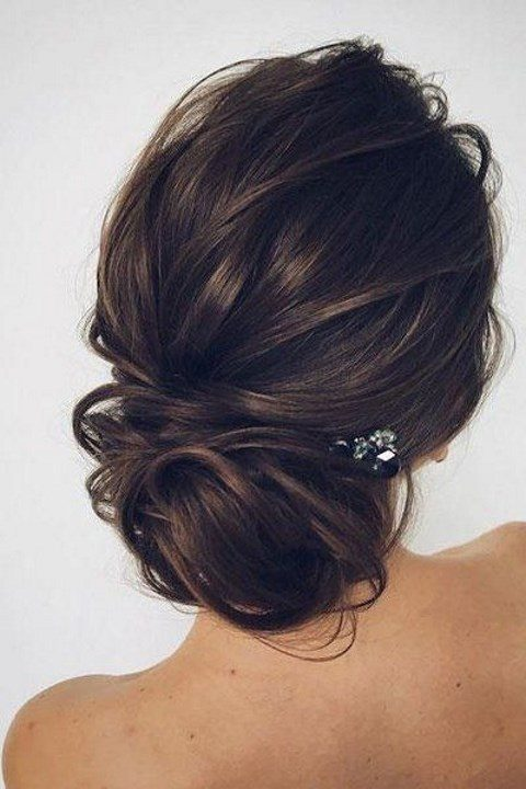 a side swept low bun with a touch of mess and a bump on top