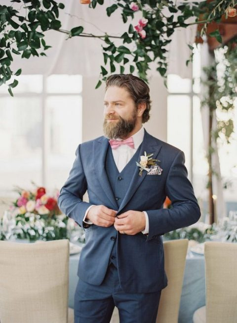 a slate grey three-piece suit, a white shirt and a pink bow tie