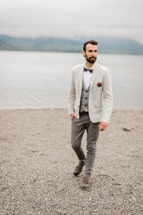 a stylish neutral look with grey pants and a waistcoat, a white shirt, a creamy blazer, a grey bow tie and grey shoes