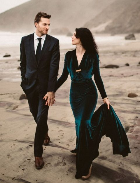 a teal velvet mermaid wedding dress with long sleeves and a train