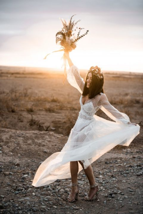 a trendy sheer pearl wedding dress with long sleeves and a lace bodysuit under it