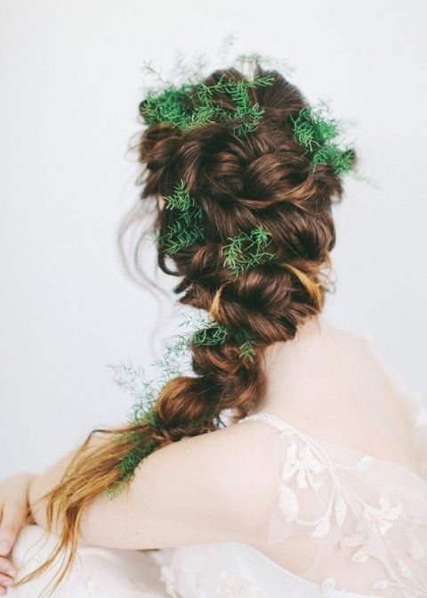 a twisted braid with evergreens tucked into it for a forest elf look