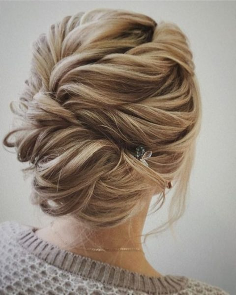 a twisted braided updo with much texture and a small hairpiece on one side