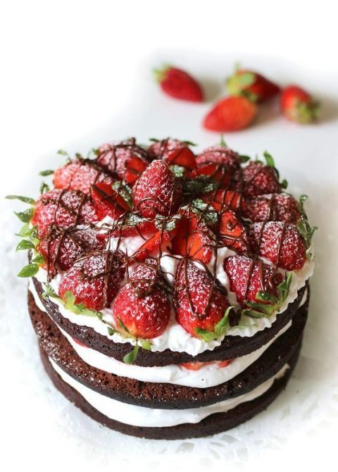 a vegan naked wedding cake with fresh strawberries, chocolate and vegan whipped cream