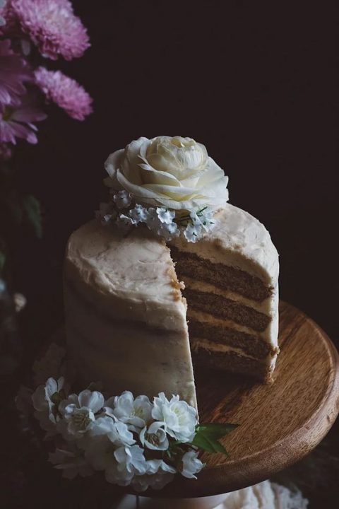 a vegan orange blossom wedding cake with salted caramel buttercream topped with fresh flowers