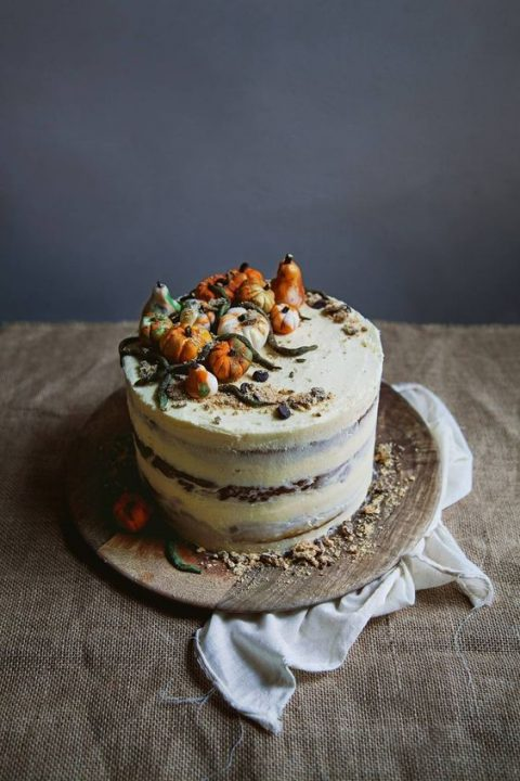 a vegan pumpkin spice layer wedding cake with fun decor on top for a fall wedding