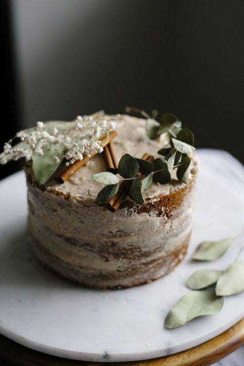 a vegan vanilla cake topped with a smooth chai spice icing and greenery, cinnamon bark and blooms