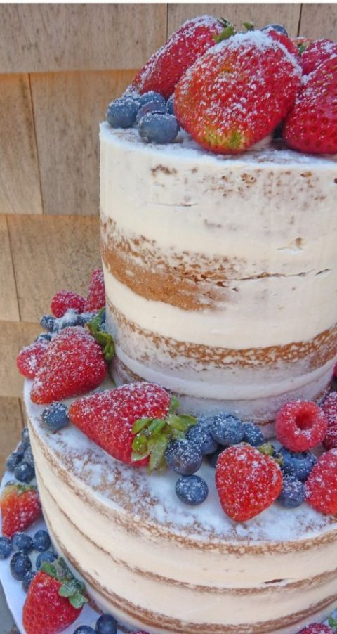 a vegan vanilla naked wedding cake with with fresh berries, a dusting of powdered sugar and vanilla frosting