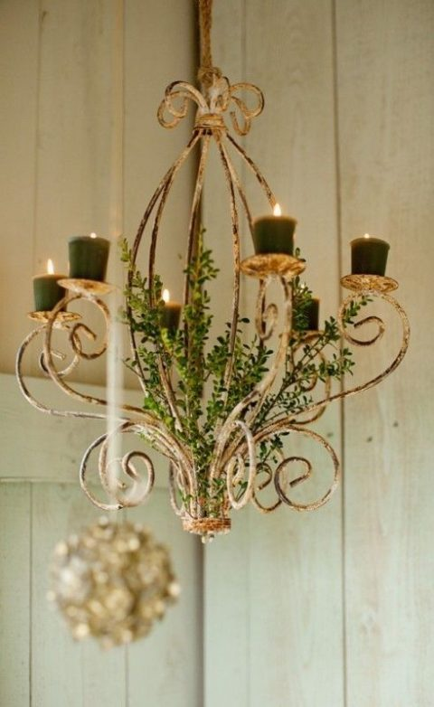 a vintage chandelier decorated with greenery and with dark green candles