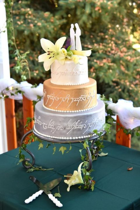 a wedding cake with an elvish love poem and fresh blooms