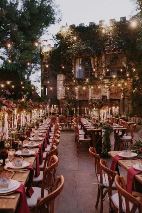 a wedding reception with burgundy touches and lots of lights in the backyard of a castle