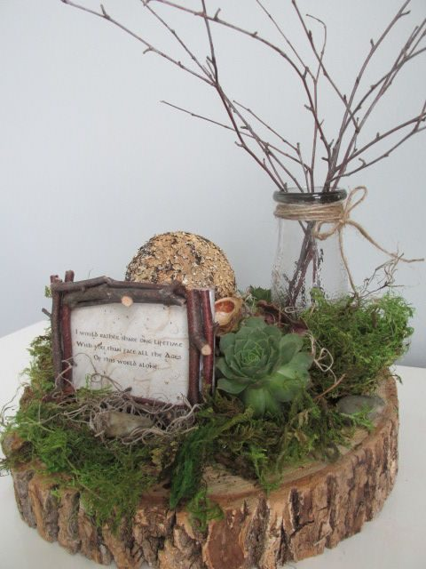 a wood slice with moss and a succulent, stone, a vase with branches and a framed quote for a centerpiece