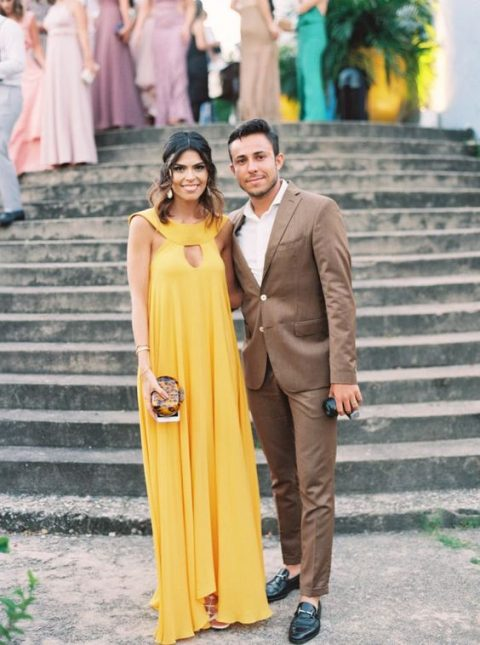 a yellow maxi dress with a catchy neckline and a cutout plis a statement clutch