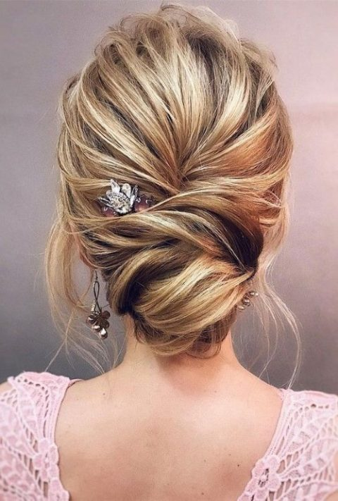 an elegant low twisted bun with a bump and some locks down is a chic option