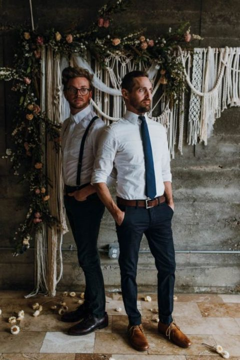 both grooms wearing black pants and white shirts, a navy tie for one guy and black suspenders for the other