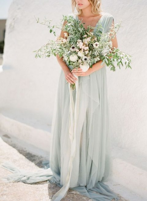 ethereal pastel green wedding dress with thick straps, draperies and layers and a long train