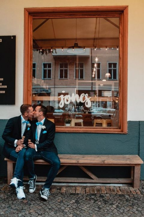 grooms wearing jackets, jeans, blue bow ties and different sneakers