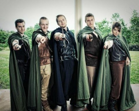 groomsmen and a groomslady dressed in elvish style and with green coats over the costumes