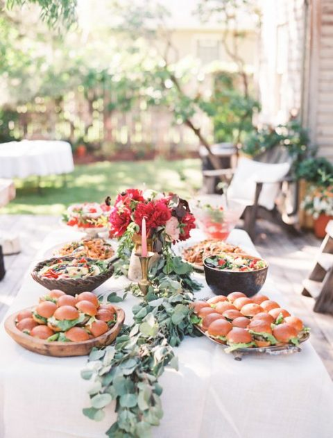a backyard buffet with a bright floral centerpiece and a fresh eucalyptus garland