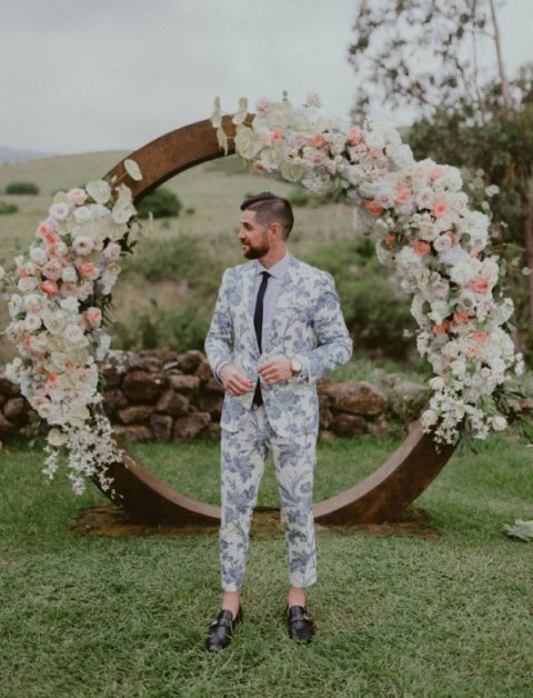 a blue floral print suit, a white shirt, a black tie and black loafers