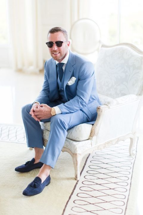 a blue three-piece suit, a navy tie, a white shirt and navy moccasins