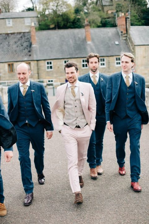 a blush groom_s suit with a checked waistcoat, a beige tie and brown shoes