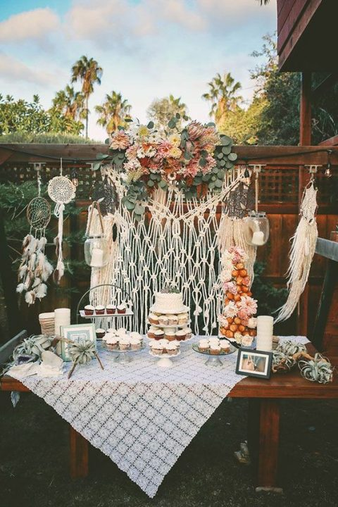a boho backyard dessert table with a macrame backdrop and dream catchers, a crochet tablecloth and bold blooms