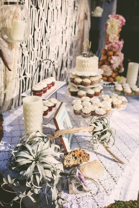 a boho bridal shower dessert table with air plants, geodes and a macrame backdrop