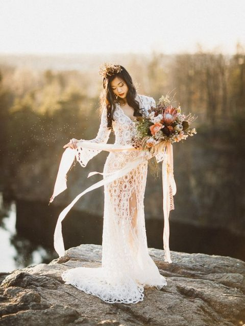 a boho lace sheath wedding gown with bell sleeves, a V-neckline and a front slit