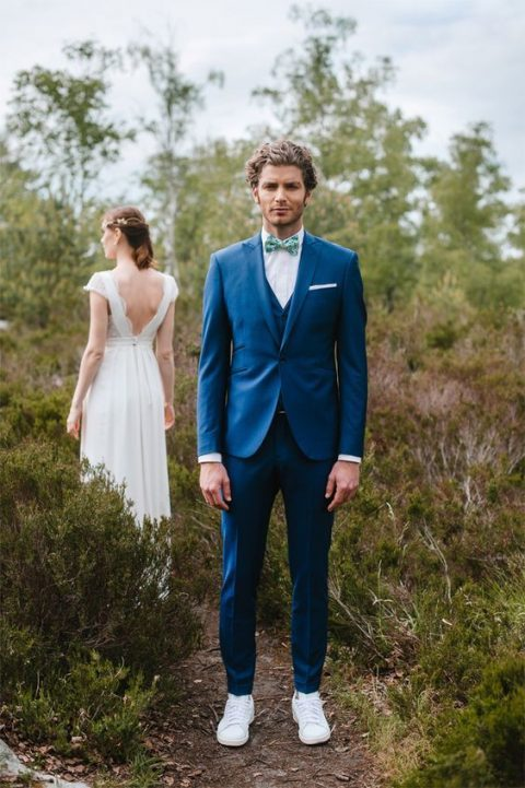 a bold blue three-piece suit, a white shirt, a colorful bow tie and white sneakers for a modern groom_s look