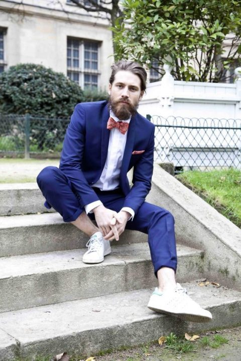 a bold navy suit, a white shirt, a printed coral bow tie and white sneakers with no socks for a bold summer look