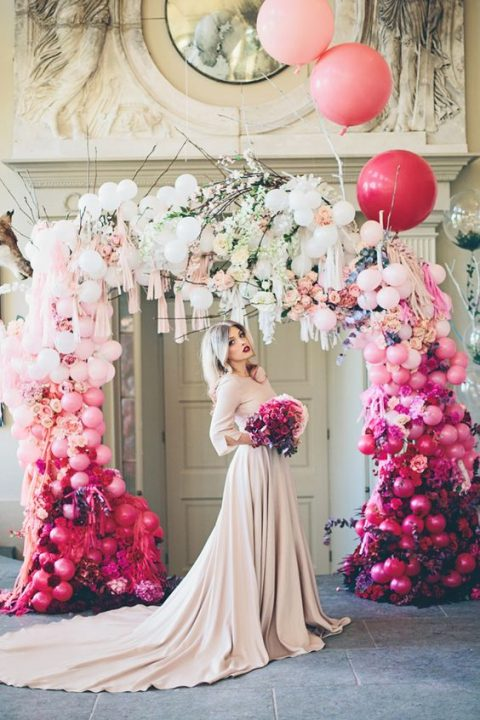 a bold ombre balloon, bloom and tassel wedding arch will make a gorgeous trendy statement in your ceremony space