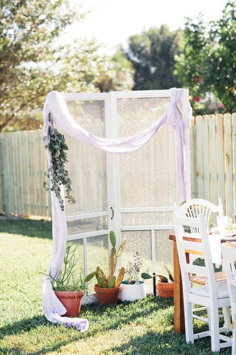 a bridal shower backdrop with vintage doors, airy fabric, eucalyptus and potted cacti