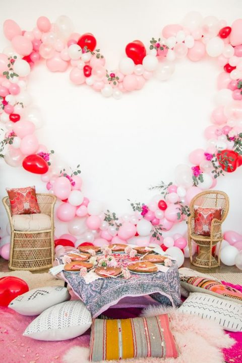 a bridal shower picnic setting with a low table, pillows, a balloon and flower heart as a party backdrop