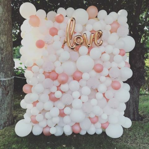 a bright and catchy balloon wedding backdrop in peachy and white with a love sign of balloons, too