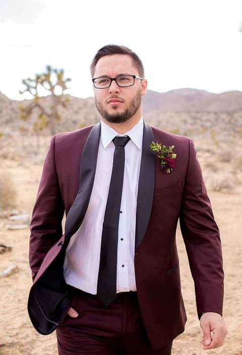 a burgundy groom_s suit with black lapels, a black tie and a white shirt
