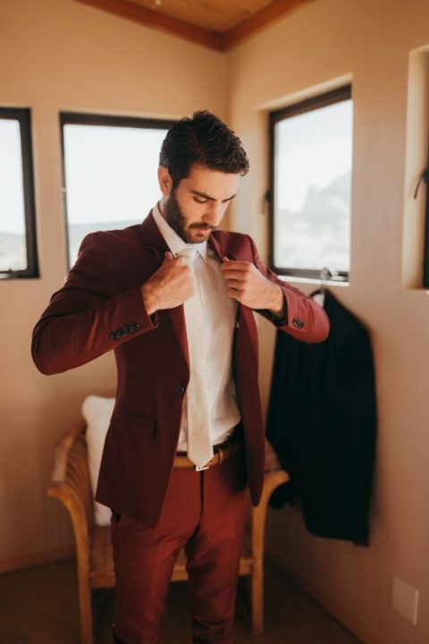 a burgundy suit, a white shirt and a white tie
